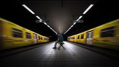 terry-donnelly-sony-alpha-7RII-man-sits-on-underground-platform-as-trains-pass-by-either-side