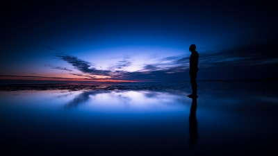 terry-donnelly-sony-alpha-7RII-silhouetted-man-stands-in-still-water-at-sunset-on-beach